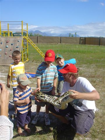 Children getting to know more about a python at Giraffe House, Cape Town